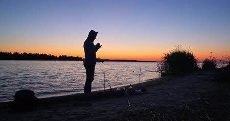 szczupak : Man fishing at sunrise on river lake Wideo