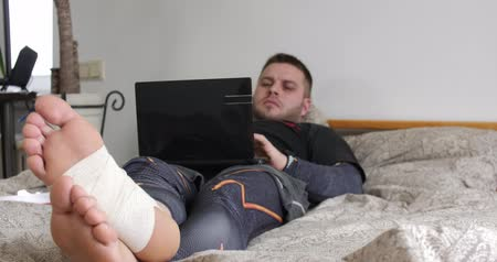 bandage : Bearded man with injured leg finish using his laptop and start thinking in the bedroom