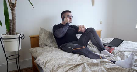 aşağıda : Serious man talking on the phone at home in the bedroom