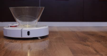 conveniência : Robot vacuum cleaner carries empty plate of sweets from left to right