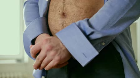 belly : Fat man zips his pants close up Stock Footage