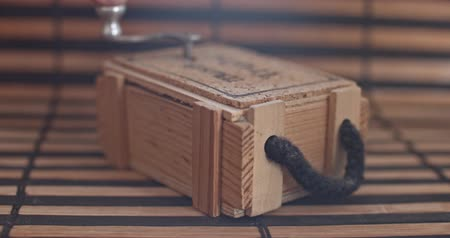 windup : Vintage mechanical music box on a little wooden plank.