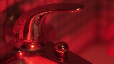 turning off : Turning on and off the water tap with red lighting. Horror concept