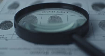 criminology : Fingerprints card and magnifier close up in motion, CSI.