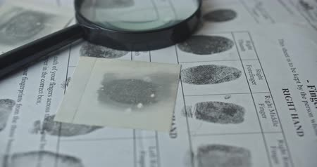 Fingerprints card and magnifier close up in motion, CSI.