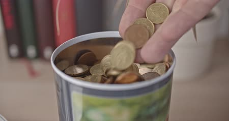 schuld : Male hand pours euro coins into a jar
