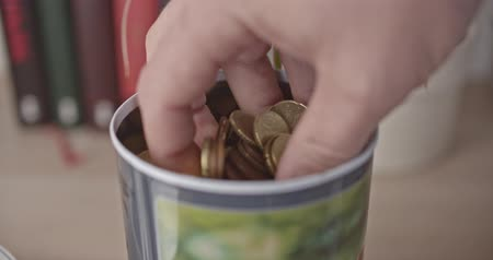 Male hand takes a handful of euro coins and bank note from a jar