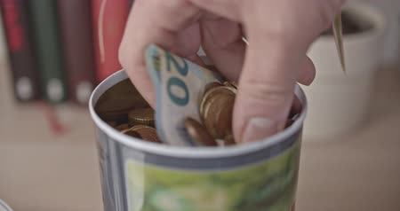 schuld : Male hand takes a handful of euro coins and bank note from a jar
