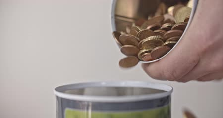 schuld : Pouring euro coins into a jar close up