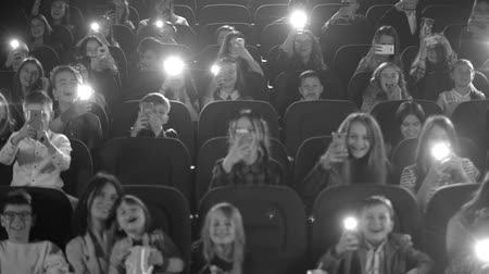 kino : Happy children in the cinema looking a cartoon and make phone flashes. Black and white shot. Wideo