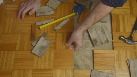 паркет : Handyman removing pieces of parquet damaged due to moisture or water