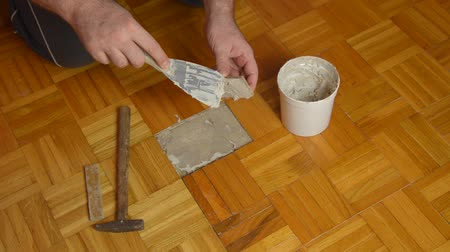 паркет : Handyman gluing pieces of parquet damaged by moisture or water