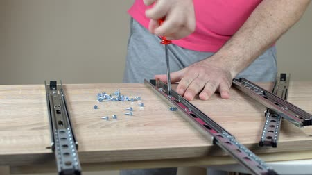 Man installing drawer slides with a screwdriver Stock Footage