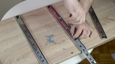 Man assembling slides for drawers with a screwdriver