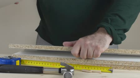 Man placing wooden dowels into a particle board shelf