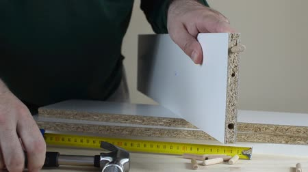 Man install wooden dowels into a particle board shelf