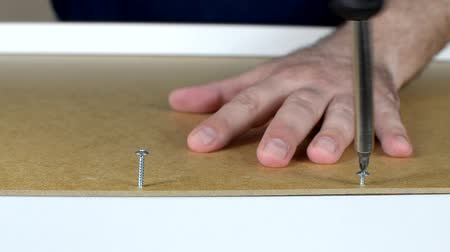 Close-up of assembling a drawer, by attaching plywood bottom to particle board sides with two screws using screwdriver