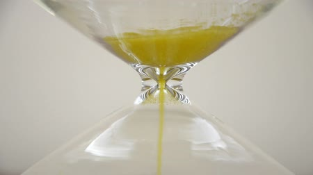 Extreme close-up of sand running down through hourglass. At 25th second of the footage the sand runs out to the hourglass representing run out of time. Stock Footage