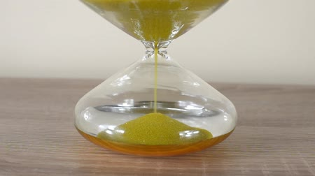 Sand running through an hourglass. Close-up. Concept of time.
