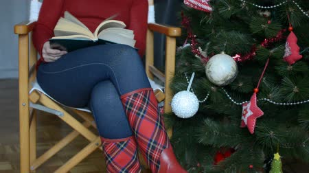 Woman in red boots with red tartan pattern sitting by decorated Christmas tree and browsing a book Stock Footage