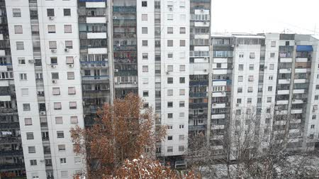 koşullar : Camera tilt-up from the first floor to the top of a building during snowing