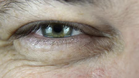 Extreme close-up footage of a mans eye, which is showing different emotions: anger, happiness, surprise. No camera movement.