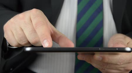 Businessman is holding and using a tablet with a touchscreen.