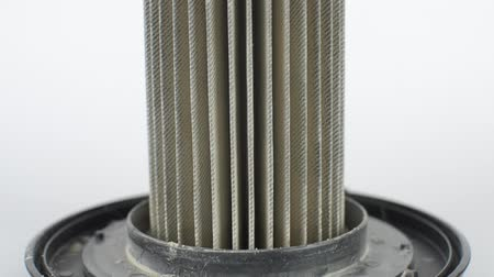 Tilt up footage of a dirty vacuum cleaner filter, full of dust and dirt, on white background.