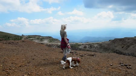Woman and her companion, dog Cavalier King Charles Spaniel, approaching to the edge of the highest viewpoint on Kopaonik Mountain, Serbia. Camera is steady at the beginning, and then start to pan to the right.