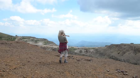 Lady hiker holding her pet dog in arms and approaching to the edge on top of Kopaonik Mountain, Serbia. Camera is steady at the beginning, and then start to pan to the right.