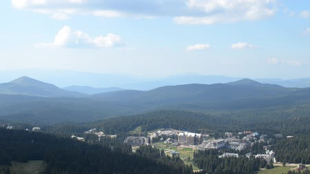 секунды : Panning shot from the top of Kopaonik mountain, to the ski resort during summer. Camera stop moving briefly and after 6 seconds of pause, continue panning to the right.