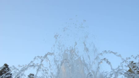 gush : Fountain water spraying up, against blue sky, in the morning Stock Footage
