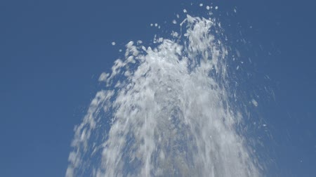 szomjúság : Water jets from a fountain changing shapes of spraying up in the air against clear blue sky