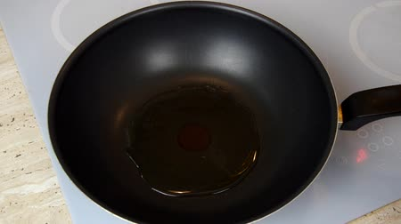 Heating cooking oil in a wok at a beginning of a cooking process Stock Footage