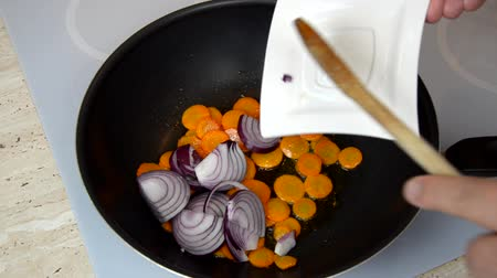 Adding onion in a wok with carrots and mixing vegetables with a mixing spoon during a cooking process Stock Footage