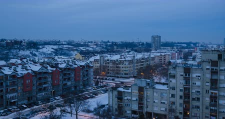 built : Time lapse footage of a nightfall in a city in winter, with roofs and streets, partly covered with snow Stock Footage