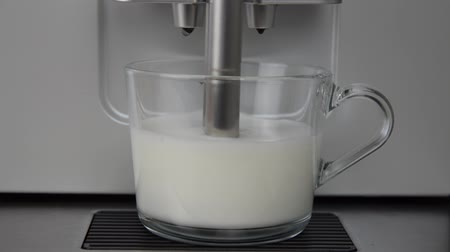 Milk frothing in a glass cup by a coffee machine