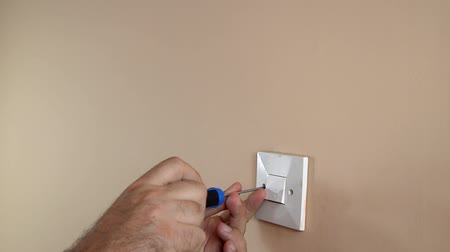 csavarhúzó : Detaching light switch from a wall with a screwdriver