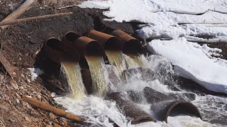 rusty pipe industrial liquid waste into river,