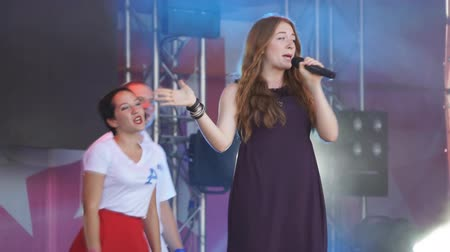 Beautiful red-haired girl sings and dances. Singer at the concert. at the festival. disc dancing girl with microphone-Russia Berezniki 14 July 2018.