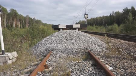 siding : Side view of passenger train arriving to a small station in the countryside, empty rail tracks nearby.