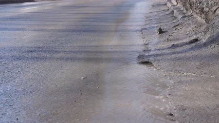 ditch : Spring stream flowing through the asphalt. Melting snow in spring. Looping Stock Footage