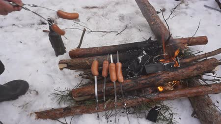 řev : unrecognizable man frying delicious juicy sausages in a snowy park.