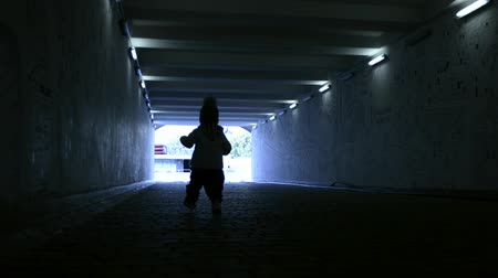 прихожая : a small child walking in the tunnel alone towards the light Стоковые видеозаписи