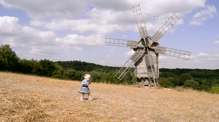 moinho de vento : a small girl walks on the field and sits down, windmill on the background Vídeos