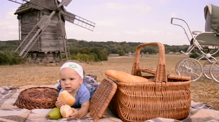 fırıldak : a small girl sitting on the ground eating bread on countryside picnic with a buggy on the background