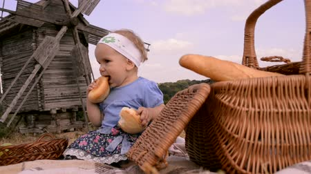 хлеб : a small girl sitting on the ground eating bread on countryside picnic with windmill on the background