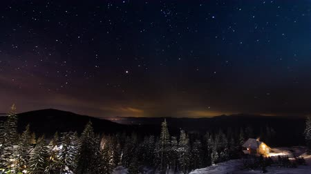 estrelado : Stars Moving Above Small House In The Mountains In WInter. Ukraine, Carpathian
