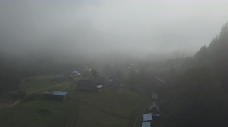 overhead view : Flying over fog and clouds in Carpathians mountains near by Dzembronya village at sunrise, Ukraine Stock Footage