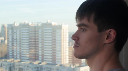 magány : Attractive man in modern glass home takes a look at the view outside Stock mozgókép